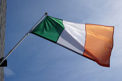 Irish flag. Fluttering in a wind against blue sky royalty free stock image