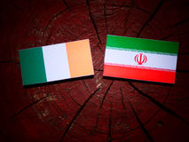 Irish flag with Iranian flag on a tree stump isolated. Irish flag with Iranian flag on a tree stump Royalty Free Stock Photography