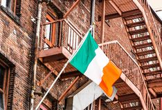 Irish Flag on Old Red Brick Buildings. An old red brick building with metal fire escape flying an Irish flag royalty free stock image