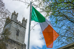 Irish flag and St Mary Cathedral tower. Irish flag fluttering in front of the tower of an Old St Mary Cathedral, Limerick, Ireland royalty free stock photo