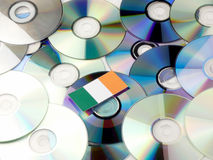 Irish flag on top of CD and DVD pile on white. Irish flag on top of CD and DVD pile stock images