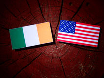 Irish flag with USA flag on a tree stump stock images
