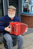 Irish gentleman playing a colorful accordion while seated on street corner,Limerick,Ireland,October,2014 Royalty Free Stock Photos