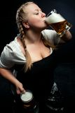 Irish girl. Drinking beer over darkbackground Royalty Free Stock Images
