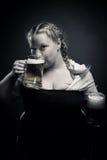 Irish girl. Pretty Irish girl drinking beer over dark background Stock Images