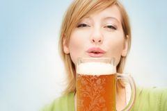 Irish girl with a beer. Smiling woman drinking a big glass beer Royalty Free Stock Photo