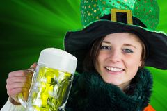 Irish girl holding beer. On green background Royalty Free Stock Images