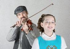 Irish Girl Listening to Fiddler. Cute Irish child listening to bearded men playing fiddle Royalty Free Stock Photos