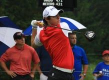 Irish golf pro Rory McIlroy. PGA pro Rory McIlroy launches his golf ball down the fairway in the rain Stock Image