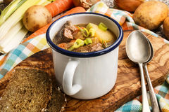 Irish lamb stew served in an blue and white enamel cup. On a wooden board Stock Photos