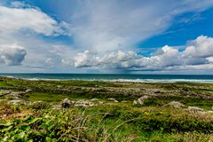 Irish landscape of the coast with limestone rocks with grass. Between Fanore and Ballyvaughan, geosite and geopark, Wild Atlantic Way, spring day in County royalty free stock photos