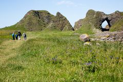 Irish landscape, green grass and cave-like rock formations, hiking family Stock Photo