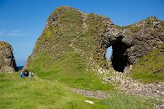 Irish landscape, green grass and cave-like rock formations, hiking family Stock Photos