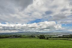 Irish landscape with green meadow against clouds, Ardmore, Ireland royalty free stock images