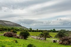 Irish landscape of meadows and farms with the sea in the background stock photo