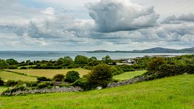 Irish landscape of sea, meadows and farms. Between Fanore and Ballyvaughan, geosite and geopark, Wild Atlantic Way, spring day in county Clare in Ireland royalty free stock photos