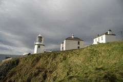 Irish lighthouse and houses Royalty Free Stock Photos