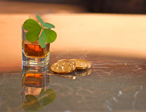 Irish Luck. Irish whiskey, clover, and gold coins on bar Royalty Free Stock Photo