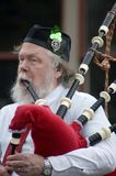 Irish Man Playing Bagpipes. Irish man with full beard playing bagpipes in St. Patrick's day parade Stock Photos