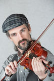 Irish Man Playing Fiddle. Serious Irish man playing a fiddle over gray background Royalty Free Stock Images