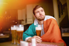 Irish Pride. Portrait of bearded man wrapped in Irish banner looking away thoughtfully, sitting at table in pub with tall glasses of craft beer Royalty Free Stock Images