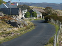 Irish rural scene. Quiet rural road and dwellings on the Atlantic drive, Achill Island, County mayo, Ireland Royalty Free Stock Images