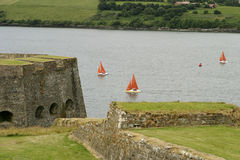 Irish Sailboat Race. A group of three small sailboats with bright red sails racing towards the start of a race near Kinsale in Ireland. In the foreground is the royalty free stock image