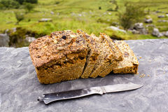 Irish soda bread. Sliced loaf of the fresh traditional Irish soda bread outside with knife aside and visible greenery on the background Royalty Free Stock Photography