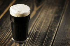 Irish Stout beer. On brown wood table Royalty Free Stock Images