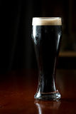 Irish stout. Served in a glass on a dark bar Stock Photography