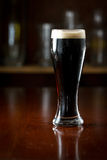 Irish stout. Served in a glass on a dark bar Stock Photos