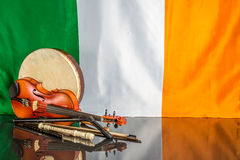 Irish Theme. A group of traditional Irish musical instruments on a black table with a Irish flag back ground Stock Images