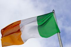 An Irish tricolour the national flag of the Republic of Ireland flying in a stiff breeze. Commonly known in Northern Ireland as the Green, White and Gold royalty free stock photos