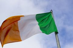 An Irish tricolour the national flag of the Republic of Ireland flying in a stiff breeze. Commonly known in Northern Ireland as the Green, White and Gold royalty free stock images
