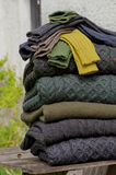 Irish woolen knits. Stack of chunky Irish wool cable knit and Aran winter sweaters plus socks in fall and winter colours in a pretty Irish rural setting Stock Image