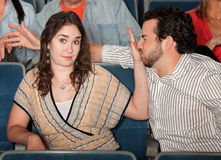 Irked Girlfriend. Irritated girlfriend stops misbehaving boyfriend in theater Royalty Free Stock Photos
