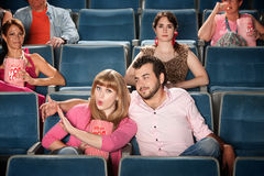 Irked Woman. Young women annoyed with boyfriend in theater Royalty Free Stock Photography