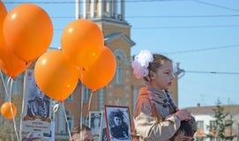 Irkutsk, Rusia - 9 de mayo de 2015: Chica joven en hombros de los padres y globos anaranjados en Victory Day en Irkutsk Imagenes de archivo