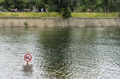 IRKUTSK, RUSSIA - JULY 15, 2019: People are walking near river at park, swimming is dangerous sign royalty free stock images