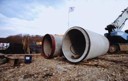 Concrete pipes. A platform with equipment for pipeline operations. Pipe penetration. royalty free stock photo