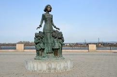 Irkutsk, Russia, 16 marzo, 2017 Il monumento all'insegnante circondato dai bambini sull'argine più basso a Irkutsk, Russia Immagini Stock