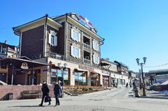 Irkutsk Ryssland, mars, 17, 2017 Folk som går nära hotell`-Kupechesky Dvor ` i gammalt som utformas 130 thfjärdedel i Irkutsk Royaltyfria Bilder
