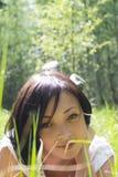 IRL bonita que coloca em um campo entre a grama fresca Fotografia de Stock Royalty Free