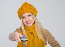 ?irl en la bufanda y el sombrero con teledirigido de la TV aislados en gris Foto de archivo libre de regalías