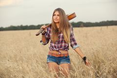 Irl with guitar goes on wheat field Stock Photography