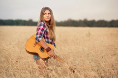 Irl with guitar goes on wheat field Royalty Free Stock Images