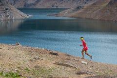 Irl runs alone among alpine lakes Stock Photography