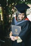 Irl som rymmer en grad, tilldelar intyg från UNITI-högskolan på avläggande av examendag Royaltyfri Foto