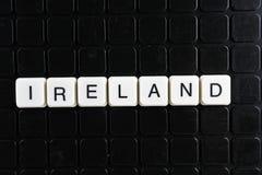 Irland-Textwortkreuzworträtsel Alphabetbuchstabe blockiert Spielbeschaffenheitshintergrund Weiße alphabetische Buchstaben auf Sch Lizenzfreies Stockfoto