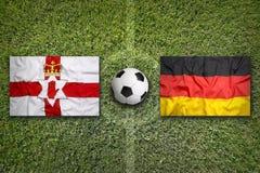 Irlanda do Norte contra Bandeiras de Alemanha no campo de futebol imagens de stock